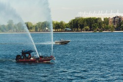 Fire department boat spraying water on river Don