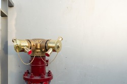 Fire department connection (90 Degree )on footpath outside the building.Red fire Hydrant And White Cement Wall Background. The fireplug standpipes system for fire extinguishing .