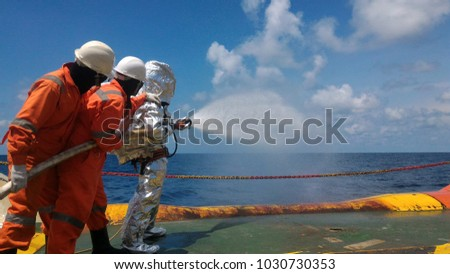 Fire drill training on board,For the crew In-ship, offshore.With fireman, fire hose, water spray, sky and blue sea and white clouds.  #1030730353