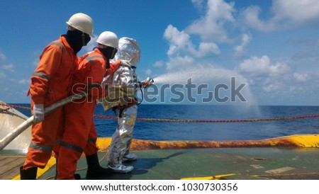 Fire drill training on board,For the crew In-ship, offshore.With fireman, fire hose, water spray, sky and blue sea and white clouds.  #1030730356