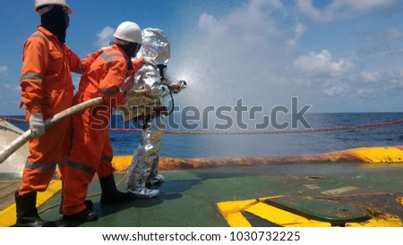 Fire drill training on board,For the crew In-ship, offshore.With fireman, fire hose, water spray, sky and blue sea and white clouds. #1030732225