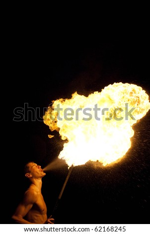 fire-eater performance on a street and audience on a dark background