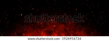 Fire embers particles over black background. Fire sparks background. Abstract dark glitter fire particles lights. bonfire in motion blur. Stock fotó ©