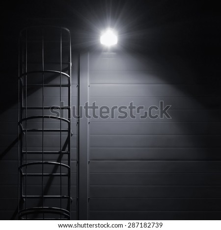 Fire emergency rescue access escape ladder stairway roof maintenance stairs night lantern lamp light shadows industrial building wall vertical closeup copy space background dark grey black