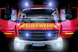 Fire engine LF10 with flashing lights and front flashers against a black background. Translation: