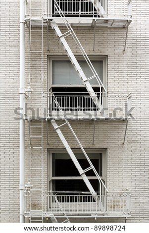 Fire escape ladder zigzagging across the face and windows of a brownstone that's been painted white.