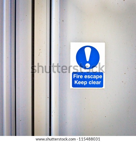 Fire escape sign on a modern door panel