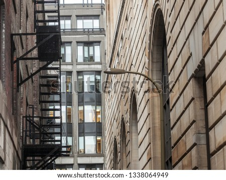 Fire escape stairs and ladder, in metal, on a typical North American old brick building from Montreal, Quebec, Canada. These stairs, made for emergency, are symbolic of the architecture #1338064949