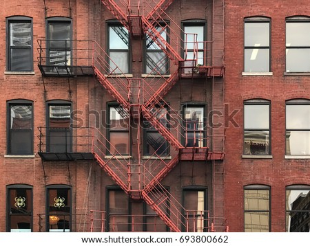 Fire Escape stairs on red brick classic building wall in Chicago City, Illinois, USA.