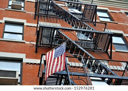 Fire escape stairs outside a New York apartment building with the American national flag