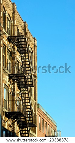 fire escapes on old tenement buildings in boston massachusetts against a blue sky
