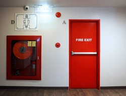 Fire exit emergency door red color metal material with alarm for safety protection and wood floor and white wall in building.
