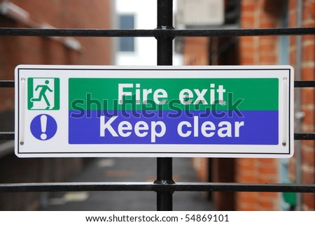 fire exit, keep clear sign hanging on a metallic fence
