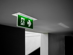 Fire exit sign. Green emergency exit sign hanging from ceiling glowing at the dark corridor near the fire escape door in the building.