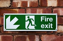 Fire exit sign on the red clay brick wall