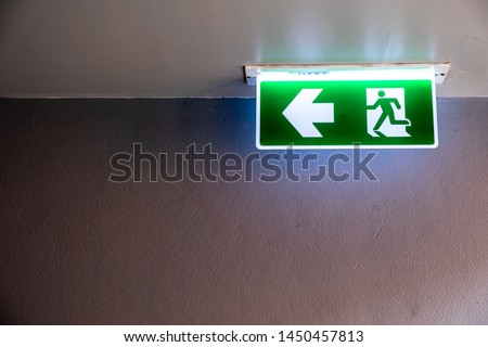 Fire exit sign with icon and arrow pointing to the left on green background hanging from the ceiling. #1450457813