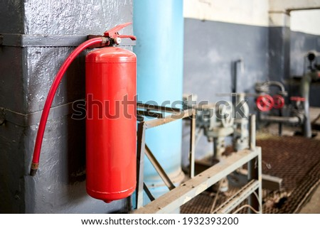 Fire extinguisher equipment in factory for fire protection system. carbon dioxide Fire extinguisher with pressure gauge on wall of production room. Concept of fire safety means of fighting fires.
