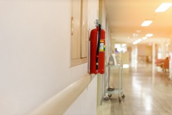 Fire extinguisher in the operating department . Install a fire extinguisher on the wall in building. Dry chemical powder fire extinguisher in corridor .a red fire-extinguisher hangs on wall .