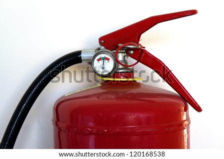 Fire extinguisher on a wall closeup under sunlight