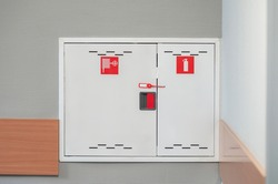 Fire extinguishers cabinet. Extinguishers cabinet on grey wall background in office building, Industrial safety concept.