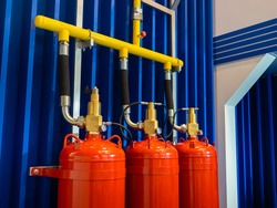 Fire extinguishing system cylinders on blue background. Industrial fire extinguishing system. Concept installation flame extinguishing systems. Fire safety at enterprise. Safety and rescue systems