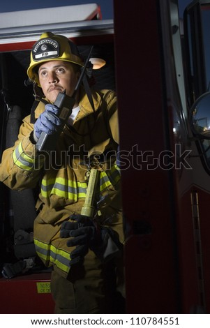 Fire fighter having conversation on walkie-talkie