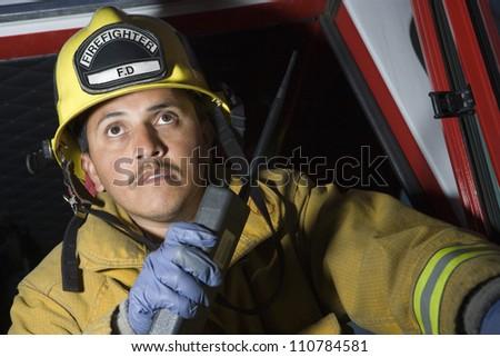 Fire fighter having conversation on walkie-talkie