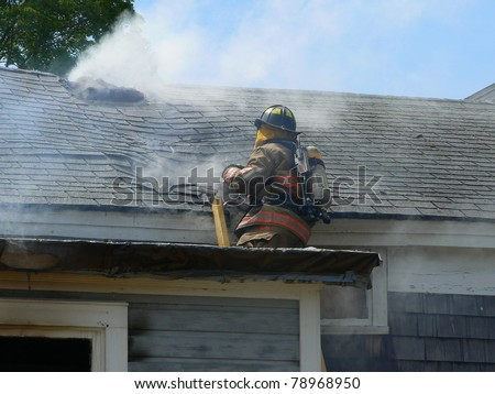 fire fighter on roof of house fire