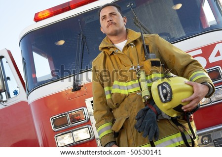 Fire fighter standing in front of fire engine