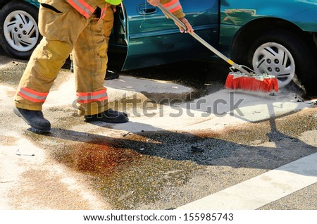 Fire fighters clean up spilled fluids at a two vehicle head on accident at an intersection in Roseburg, OR on August 27, 2013