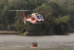 Fire Fighting and Rescue Helicopter with Bambi Bucket are Carrying Water from Reservoir to put out a Forest Fire