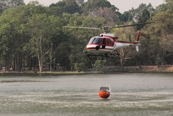 Fire Fighting and Rescue Helicopter with Bambi Bucket are Carrying Water from Reservoir to put out a Forest Fire.