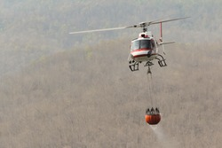 Fire Fighting and Rescue Helicopter with Bambi Bucket Carrying Water to put out a Forest Fire with Mountain Background, Copy Space
