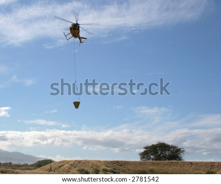 Fire-fighting helicopter in flight with water bucket responding to an emergency