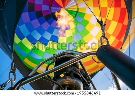 Fire from a gas burner in a hot air balloon. Hot gas inflates a bright, multi-colored balloon. Bottom view