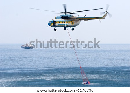 fire helicopter taking water from the sea to its special tank