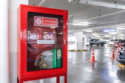 Fire Hose Reel box in the corner of Car Parking., The White Thai Language letter in the middle of the red box means FIRE HOSE REEL.