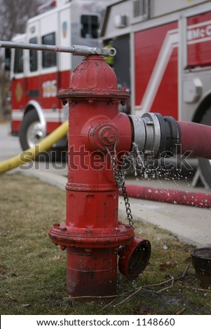 Fire Hydrant with Shallow Depth of Field firetruck in the background with water