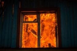 fire in a window in a wooden house