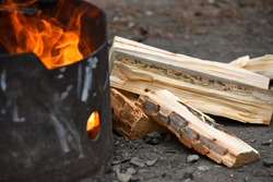 Fire in black metal pit at campsite with chopped wood