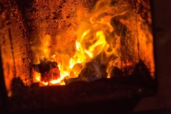 Fire in fireplace. Close up of hot red fire from coal in central heating stove.