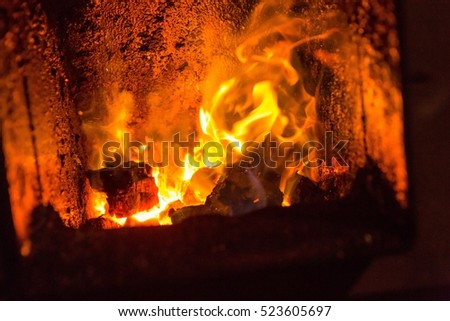 Fire in fireplace. Close up of hot red fire from coal in central heating stove. #523605697