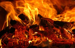 Fire lit in the fireplace of a campsite with a beautiful bright red color, detail