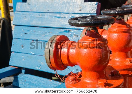 Fire monitor valves painted in red near a wooden bench onboard a construction barge at oil field