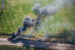 Fire on highway  - strong black smoke rises to the sky, flames are visible - two trucks caught fire on a highway and burn out completely - aerial view