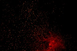 Fire particles effect dust debris isolated on black background, motion powder spray burst. fire flames with sparks. Burning red hot sparks fly from large fire in the night sky.  light and life.