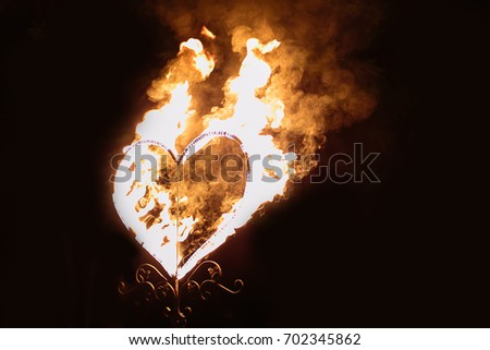 fire performance, feelings, symbolism concept. in the dark there is a big heart covered in bright orange flames like symbol of love that always wins world evils #702345862
