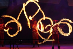 Fire performers juggling with burning pois, making circular movements