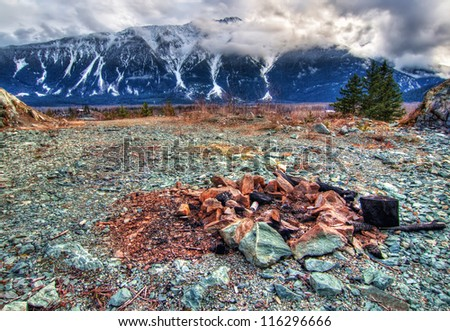 Fire pit with snow mountains and clouds in background