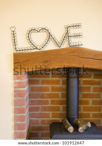 fire place with logs and the word love on the wall - stock photo